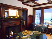 Corner of dinning room with fire in fireplace and table and chairs with fruit bowls on it.
