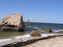 Long Island Sound picture with a sail boat in the distance behind a huge rock in the sound.  There is sand and rocks on the beach and the waves are breaking on them.