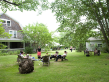 Wide shot of west yard lawn with inn, trees, seats and people in groups sitting around.