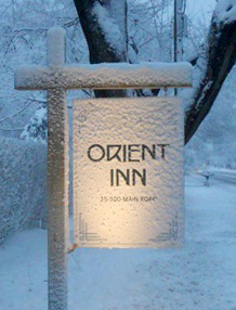Exterior orient inn wooden hanging sign with a snowy background.