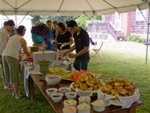Catering tent with food on table and people taking bagels, buns fruit and yogurt