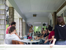 People at tables eating and drinking and socializing of west porch.