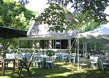 Table with table cloths and chairs around the tables with tent and umbrellas in west yard and west side of inn is visible.